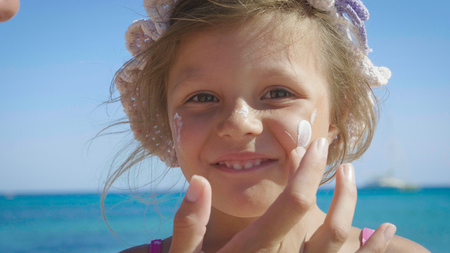 Cute little girl in panama, sun protection cream, background of sea. Concept: children, childhood, summer, freedom, kids, baby, summer.