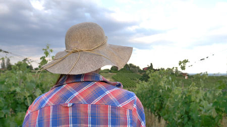 Beautiful smiling girl (woman) farmer looking over grape fields, in straw hat and in shirt, greens background. Concept ecology, wine, bio product, inspection, water, natural products, agriculture Reklamní fotografie