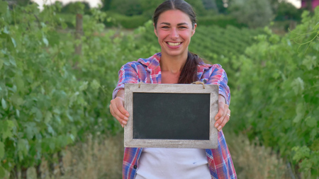 Beautiful girl (woman) farmer smiling watching the grape fields, holding a black board, in a shirt, greens background Concept ecology wine bio product, inspection, water, natural products, agriculture 版權商用圖片
