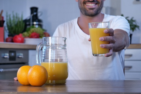 A man in a white kitchen with a glass of orange juice. A genuine fruit juice that is good for the body. Concept of: healthy drinks, diet and regular life