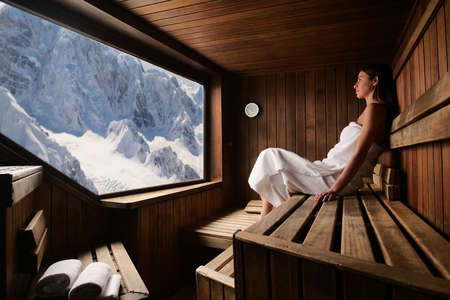 A beautiful woman wearing a white towel takes a sauna: The sauna is made of wood. Concept of: relax, vacation, wellness center.