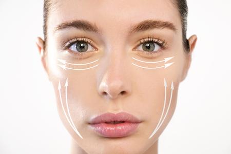 Retrato de una bella mujer con cremas antiarrugas o cirugía de cerca. Concepto de: cirugía, cremas.