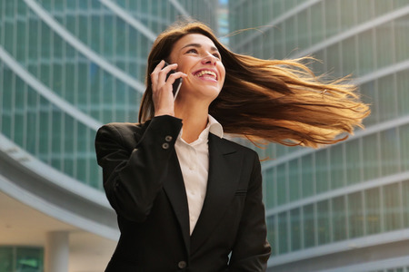 A businesswoman in a business suit, exulted by happiness after finishing the deal, in the background skyscrapers. Concept of: business, technology, economy and work and success