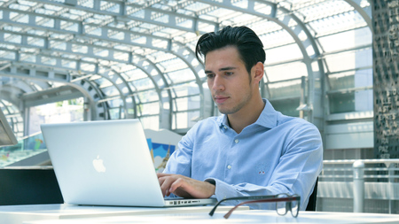 Young handsome businessman (student) in a blue shirt sitting on a laptop, serious, smiling. Concept: new business, business relationships, career growth, success, online work, station.