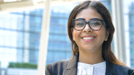 Portrait of young beautiful business woman (student) in suit, glasses, smiling, happy, walking down stairs, steps, on building background. Concept: new business, communication, Arab, banker, manager.