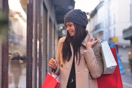 A young and beautiful girl enjoys shopping while shopping for the city's shops. The girl holds many all colored handbags. Concept of: shopping, fun, leisure, discounts and balances.