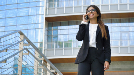 Young beautiful business woman (student) in a suit, smiling, happy, going down stairs, steps, talking on the phone, writing a message. Concept: new business, communication, Arab, banker, glasses, call