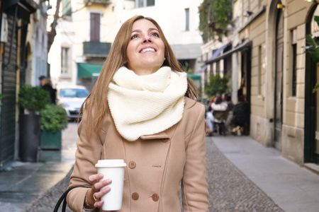 A woman with a coffee, she is dressed in elegance, she walks through the streets of the city while she drinks an American coffee and holds the bag in her hand. Concept of: businesswoman,