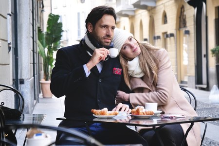 A couple of lovers have breakfast in a bar while sitting outdoors and looking at the phone. Concept of: love, valentines day, technology