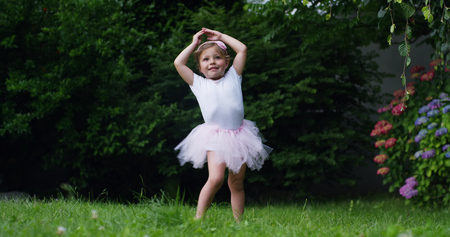 On a sunny spring day a baby girl dressed as a dancer plays tries to stand up and take her first steps alone without a mother Archivio Fotografico - 112992941