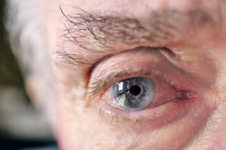 Macro shot of an elderly gentleman looking into the camera. Concept of: life, eyes, optic and care for older people.