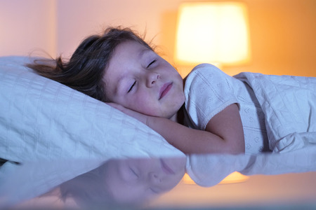 A little girl sleeps at night in her bedroom. Concept of: peaceful dreams, good sleep, relaxation, home.