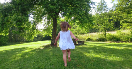 cute toddler girl running happy on the green widow in a woods. Concept of love for nature, protection of kids, innocence, fun, joy, carefree childhood, freedom