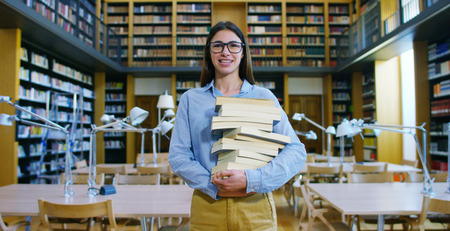 Portrait of a beautiful young woman smiling in a library holding books after doing a search and after studying. Concept: educational, portrait, library, and studious.