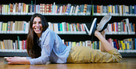 A beautiful young woman studying in a happy and carefree library. Concept: educational, portrait, library, and studious, relax.