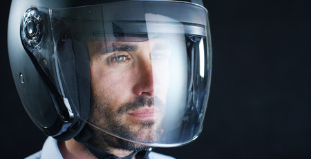Portrait of a professional rider or motorcyclist, in a protective black helmet, on a black background. Concept: driver, drive, speed, defense, space, airplane, pilot, protective suit, extreme, sports. Stockfoto