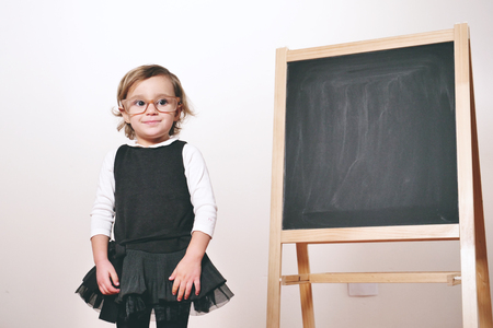 A little girl dressed as a teacher in front of a small blackboard holding a lesson in economics, marketing, teamwork, mathematics. Concept of: educational, school, business and love for study.