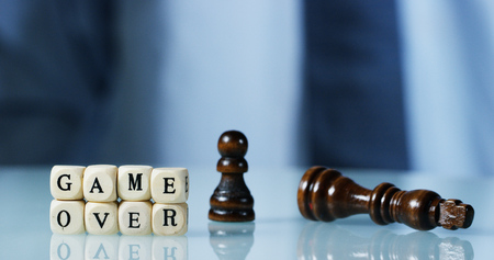 game made of wooden letters and held by hand. concept of evil and market crashed financial affairs Stock Photo
