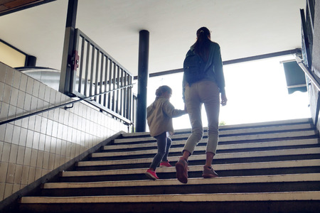 A woman and a daughter are walking in a corridor of the metro station. Banco de Imagens