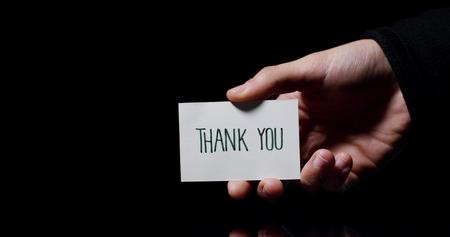 "A hand showing a card saying: ""Thank You"". business concept, thanks, records website."
