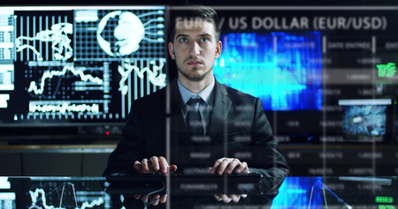 a young man controls the financial workflows and watch the monitors and writes to see stock quotes in his office Banco de Imagens