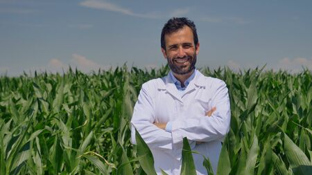 A plant specialist, examines the corn fields, a white coat takes a sample of leaf moisture, a background of greenery