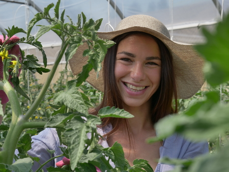 Portrait of a beautiful young woman in a straw hat. Concept: bio products, natural products, fresh, delicious, fruits, vegetables, grow, water, plants.