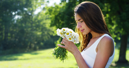 A woman surrounded by greenery has collected flowers and count them in thought, thinking about his love thinks of his life that he spends. flowers that bring back memories of the good memories.