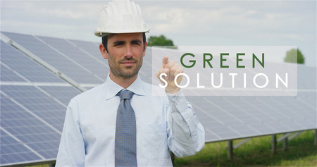 "A futuristic technical expert in solar photovoltaic panels, selects the ""Green solution"" function using pure renewable energy. The concept of remote support technology, ecology and remote control Banco de Imagens"