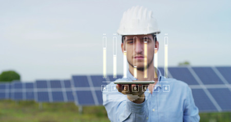 In a field photovoltaic solar panels an engineer, thanks to holography and augmented reality. Concept: renewable energy, technology, electricity 写真素材