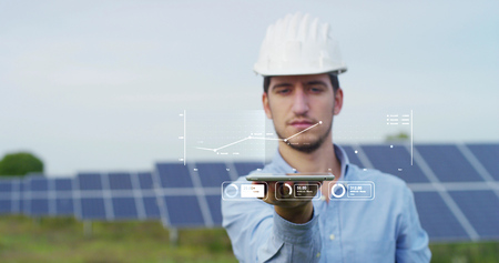 In a field photovoltaic solar panels an engineer, thanks to holography and augmented reality. Concept: renewable energy, technology, electricity Archivio Fotografico