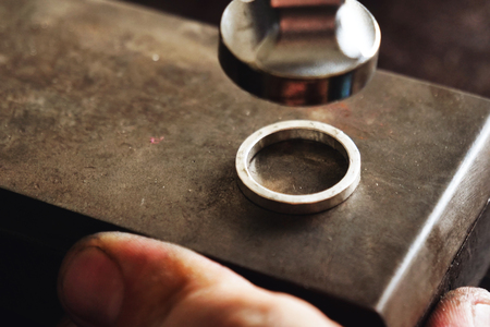 Close up of a goldsmith's hand making a gold or silver ring or a diamond using goldsmith's tools. For this work it takes precision and patience. Concept of: tradition, luxury, jewelry. Imagens