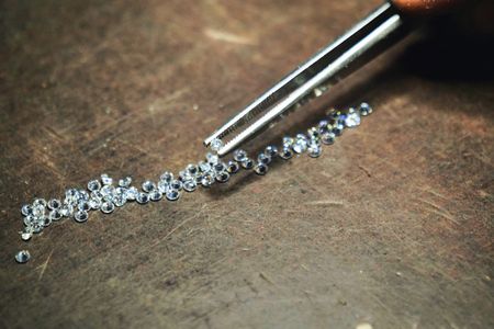 Close-up of a goldsmith who with professional tweezers, checks the diamonds that he will use for the production of handmade luxury jewelery. Concept of: tradition, luxury, jewelry. Banco de Imagens