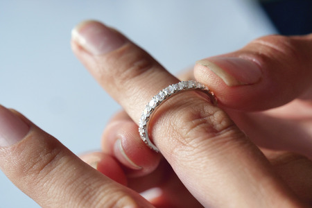 Close-up of a beautiful woman wearing a precious diamond ring. Concept of: wedding, luxury, jewelry.