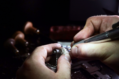 Close up of a goldsmith's hand making a gold or silver ring or a diamond using goldsmith's tools. For this work it takes precision and patience. Concept of: tradition, luxury, jewelry. Archivio Fotografico