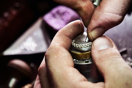 Cerca de la mano de un orfebre haciendo un anillo de oro o plata o un diamante con herramientas de orfebre. Para este trabajo se necesita precisión y paciencia. Concepto de: tradición, lujo, joyería.