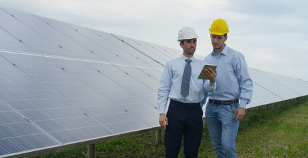 Two technical expert partners in solar photovoltaic panels, remote control performs routine operations to monitor the system using clean, renewable energy. The concept of remote support technology. Stockfoto