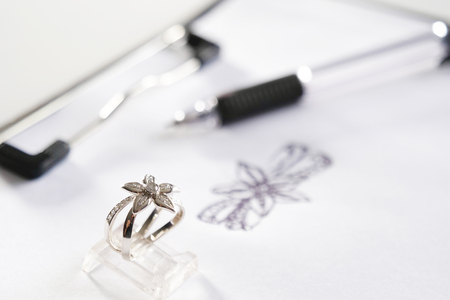 Close-up of a precious diamond ring depicting a flower; in the background we can see the drawing from which it was inspired. Concept of: wedding, luxury, jewelry.