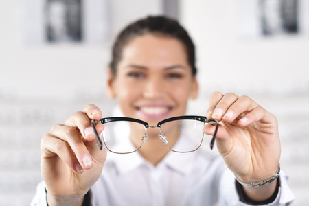 Portrait of an ophthalmologist doing a visual examination for a customer at an optical center. Try the spectacles to the patient. Concept of: medical examination, assistance, optics and customer care.