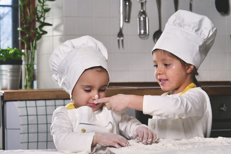 Two little girls in the kitchen prepare food, a dessert for the family. They start to cook and start each other. Concept of: cooking classes, family, education.