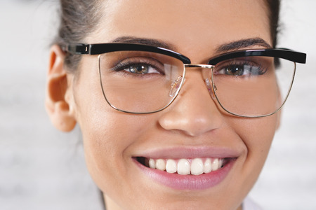 A woman in an optical center smiling while looking at the camera happy with the ophthalmologists visit and the eyeglasses just bought. Imagens