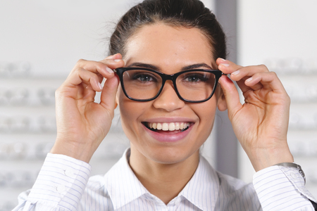 A woman in an optical center smiling while looking at the camera happy with the ophthalmologist's visit and the eyeglasses just bought.