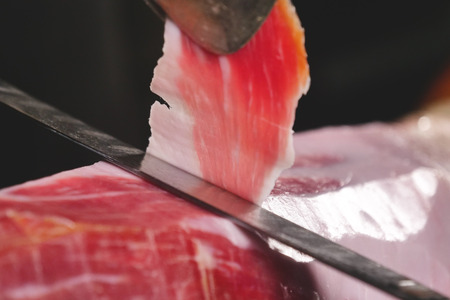 Close up macro of a chef who cuts a slice of ham. Concept of ham, food, Spain and Italy, catering. Stock Photo