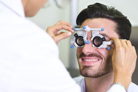 ein Augenarzt, der für einen Kunden in einem optischen Zentrum eine visuelle Untersuchung durchführt. Probieren Sie die Brille dem Patienten aus. Konzept von: ärztliche Untersuchung, Assistenz, Optik und Kundenbetreuung.