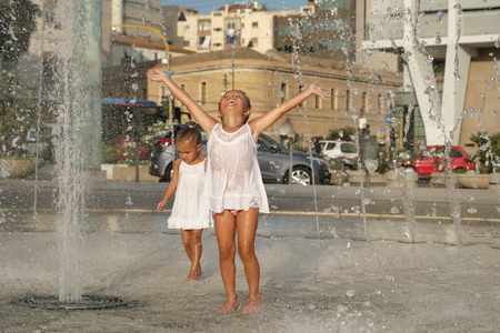 Two little girls are having fun in a fountain, smiling in white background.