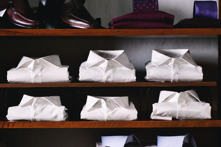 Close up of new white folded shirts on a shelf. concept: fashion, tailor, shopping