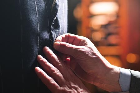 Portarit van een kleermaker tijdens het maken van een pak met behulp van het meetlint. Concept: Mode, maatwerk, winkel