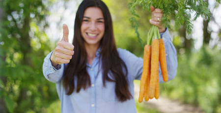 The young girl is holding a biological product of carrots, hands and carrots soiled with earth. Concept: biology, bio products, bio ecology, grow vegetables, vegetarians, natural clean and fresh product. Stok Fotoğraf