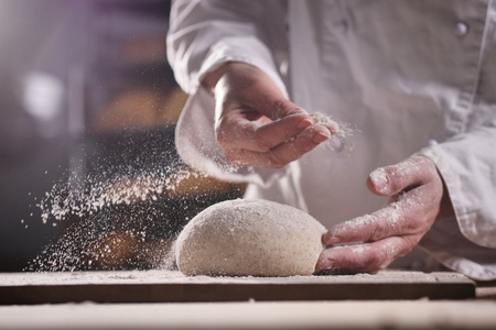 An experienced chef in a professional kitchen prepares the dough with a flour to make the organic Italian pasta. the concept of nature, Italy, food, diet and bio. 免版税图像