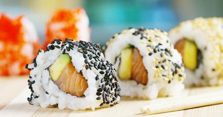 Macro shot of sushi, sashimi, uramaki and nighiri.typical Japanese dish consisting of rice, salmon or tuna, shrimp and fish on black background.Concept: Japanese restaurant, sushi, oriental tradition